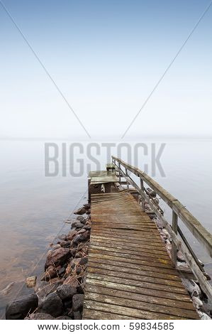 Old Ruined Wooden Pier On Saimaa Lake In Foggy Morning