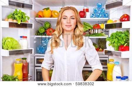 Woman chosen milk in opened refrigerator, cool new fridge full of tasty organic nutrition, female preparing to cook, healthy eating concept