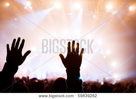 Musical concert, silhouette of man hands raised up, enjoying music in the club, luxury night performance, active lifestyle, having fun concept