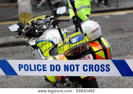 Policeman and police motorcycle behind cordon tape at an accident or crime scene