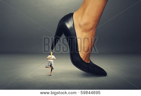 calm businesswoman under big heel. isolated on white background