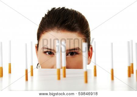 Young woman looking on cigarettes standing on white table.