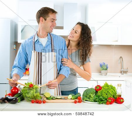 Cooking. Young Man cooking. Happy Couple Cooking Together - Man and Woman in their Kitchen at home Preparing Vegetable Salad. Diet. Dieting. Healthy Food Tasting