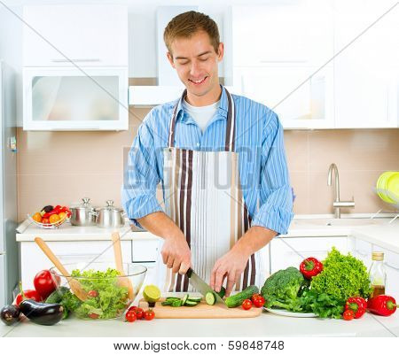 Young Man Cooking in the kitchen. Healthy Food - Vegetable Salad. Diet. Dieting Concept. Healthy Lifestyle. Cooking At Home. Prepare Food