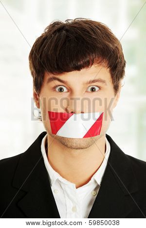 Freedom of speech concept. Young handsome businessman with red and white tape on his mouth.