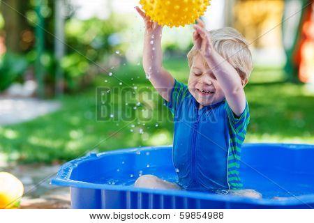 Little Toddler Boy Having Fun With Splashing Water In Summer Garden Pool.