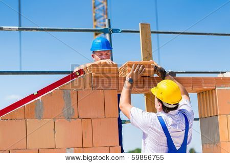 Two bricklayers or builders or workers building or bricklaying or laying a stone or brick wall on a construction or building site.