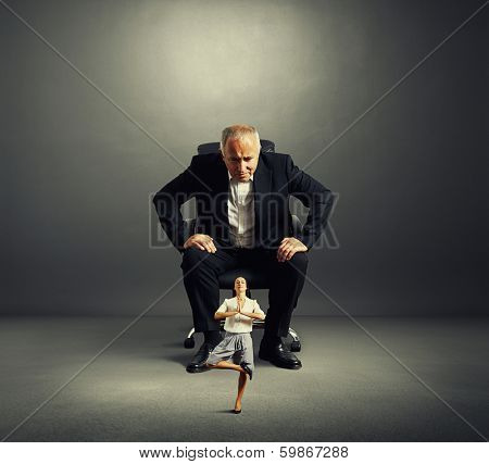 senior businessman sitting on the office chair and scrutinizing meditation businesswoman