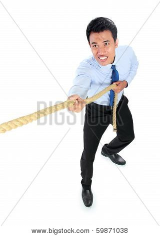 Young Businessman Pulling A Rope While Standing