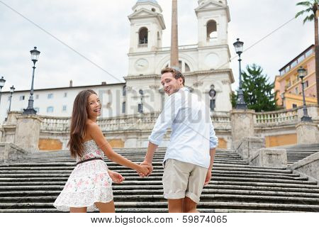 Couple holding hands on Spanish Steps, Rome, Italy. Happy romantic couple. Young interracial couple walking on the travel landmark tourist attraction icon during their romance Europe holiday vacation