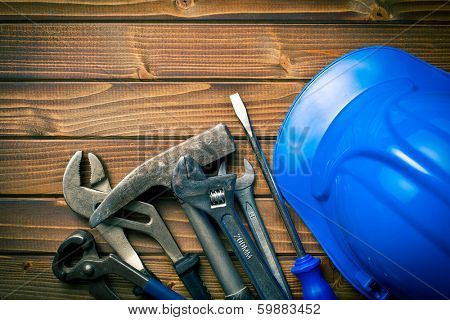 hard hat with various working tools on wooden background