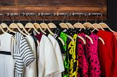 picture of woman red blouse  - Many blouses on hangers in the dressing room - JPG