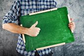 Man Holding Green Chalkboard And Showing Thumb Up