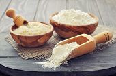 pic of cereal bowl  - Raw rice and flour in bowls with scoop on wooden background - JPG