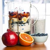 pic of smoothies  - Prepared smoothies and healthy smoothie ingredients in blender with fresh fruit ready to blend on kitchen table - JPG