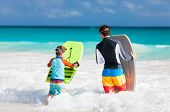 foto of boogie board  - Father and son running towards ocean with boogie boards - JPG