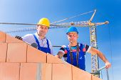 Two proud construction site workers - or bricklayers - standing on house project directing a crane w