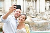 image of two women taking cell phone  - Tourist couple on travel taking selfie photo by Trevi Fountain in Rome - JPG