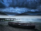 stock photo of old boat  - Stormy sky landscape over misty mountain lake with old boat on lake shore - JPG