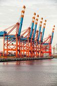 picture of lifting-off  - Deserted port terminal in a harbour for loading and offloading cargo ships and freight with rows of large industrial cranes to lift goods off the decks and from the holds - JPG