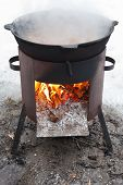 stock photo of brazier  - cooking stew on outdoor mobile brazier in winter - JPG