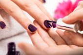 stock photo of nail  - Woman having a nail manicure in a beauty salon with a closeup view of a beautician applying rich purple nail varnish with an applicator - JPG