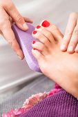 foto of pumice-stone  - Woman having a pedicure treatment at a spa or beauty salon with the pedicurist massaging the soles of her feet with a pumice stone to cleanse dead skin and stimulate the tissue