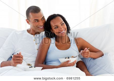 Cheerful Couple Having Breakfast On Their Bed
