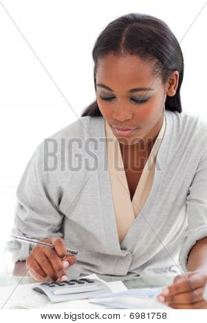 Charming Businesswoman Using A Calculator At Her Desk