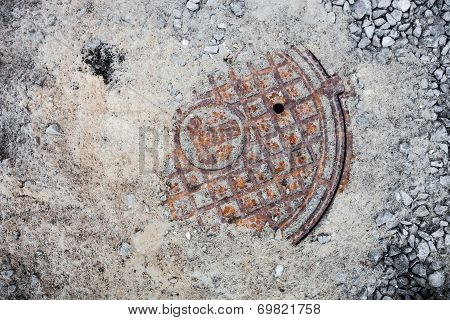 Manhole With The Cover In The Sand And Crushed Stones