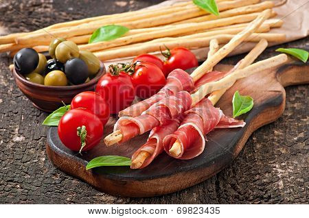 Grissini bread sticks with ham, olives, basil on old wooden background