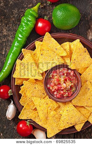Mexican nacho chips and salsa dip in bowl on wooden background