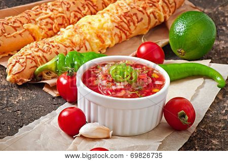 Salsa dip in bowl of bread and cheese sticks