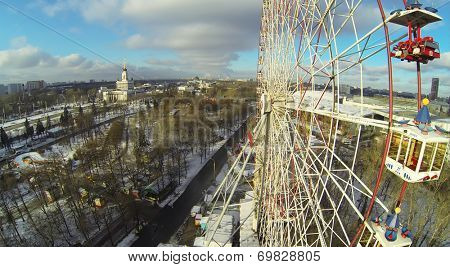 MOSCOW, RUSSIA - NOVEMBER 30, 2013: Ferris wheel at an amusement park in Russia Exhibition Center, aerial view. The park was created in 1995 for the 850 anniversary of Moscow