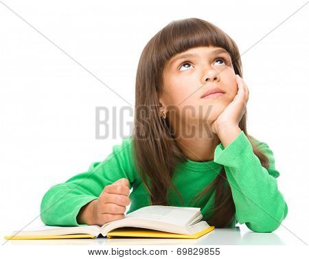 Young girl is daydreaming while reading book, isolated over white
