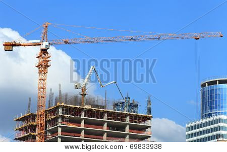 High-rise building under construction with crane and concrete pump.