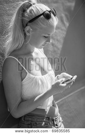 Attractive teenage girl using smartphone outdoor