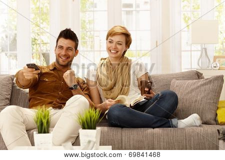 Happy young couple watching tv at home.