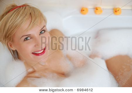 Smiling Blond Woman Lying In Bubble Bath