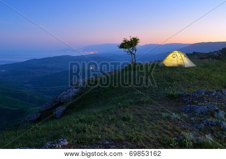 Night landscape with tourist tent. Camping in the mountains