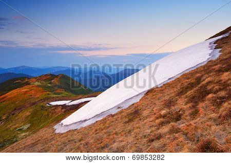 Spring landscape in the mountains. Snowfield on a mountain slope