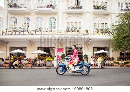 Vietnamese girl wearing long dress ( ao dai ) is riding on the old bike
