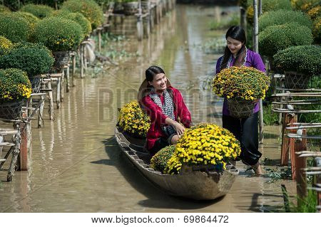 Girls collect flowers for selling at TET holiday