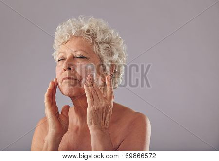 Mature Caucasian Woman Applying Anti-wrinkle Face Cream.