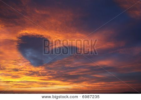 Sunset cloudy sky with a heart shaped cloud formation