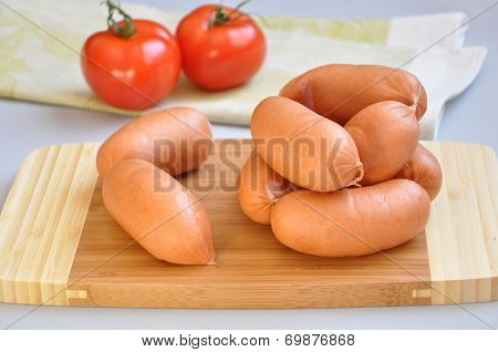 Delicious Sausages On A Cutting Board And Ripe Tomatoes
