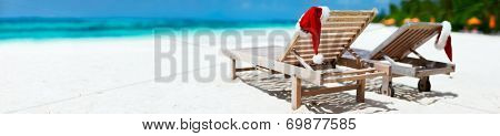 Panorama of two sun loungers with Santa hats on beautiful tropical beach with white sand and turquoise water, perfect Christmas vacation