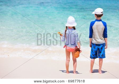 Little kids in sun protection rash guards on tropical beach during summer vacation