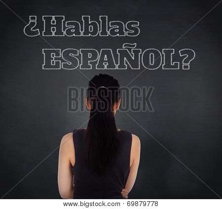 Composite image of standing businesswoman against blackboard, Do you speak Spanish?