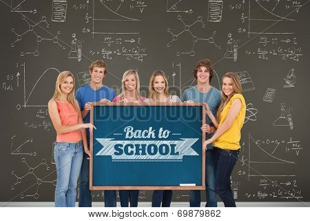 Composite image of a A group of people holding blackboard with message on wooden board